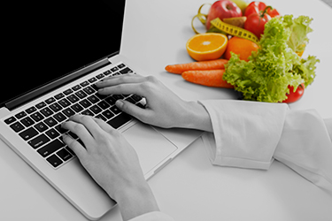 female-nutritionist-working-on-laptop-PAKSY89